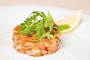Salmon tartare with arugula, capers and lemon